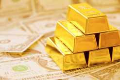 Gold bars on a pile of money
