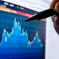 hand with a pen pointing to a stock chart