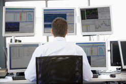 Trader at desk with multiple monitors